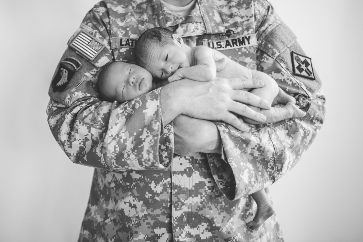 Newborn photography session of twins being held by their father who is a soldier in the military.