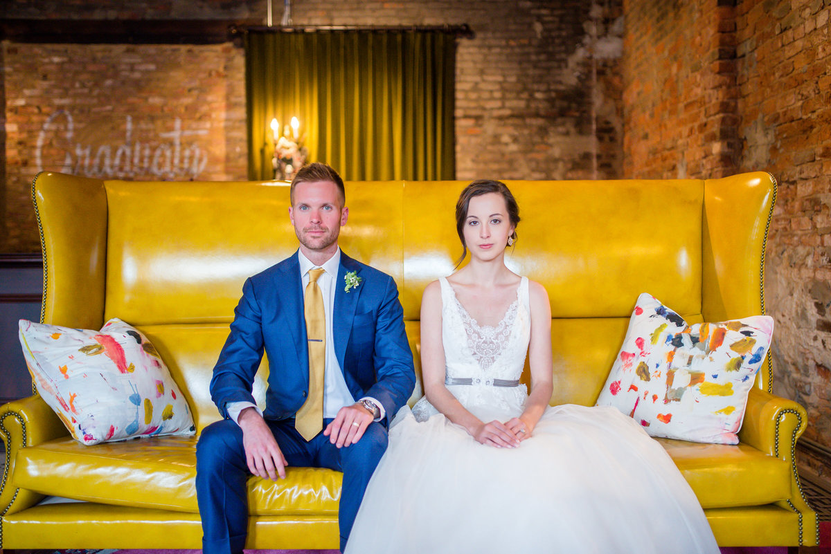 couple sitting on yellow couch wedding at graduate athens ga by eliza morrill