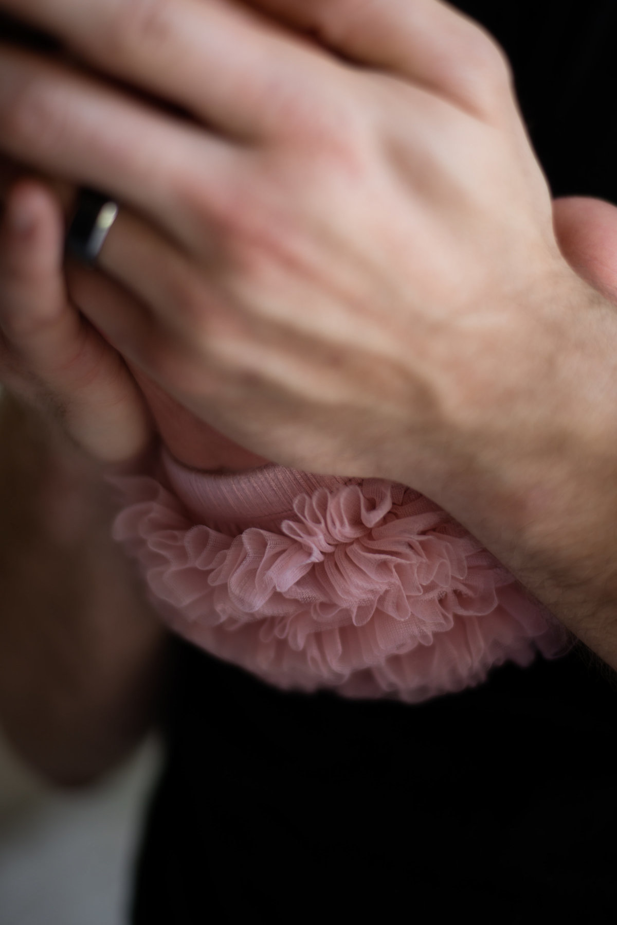 Closeup color photo of baby girl's ruffled  bottom pink diaper cover as dad's arms are seen holding her suspended from his chest.