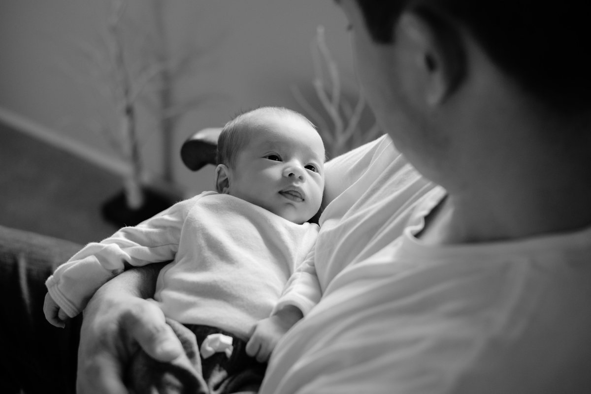 Black and white photo of baby boy laying in dad's arms as he gently stares back at him