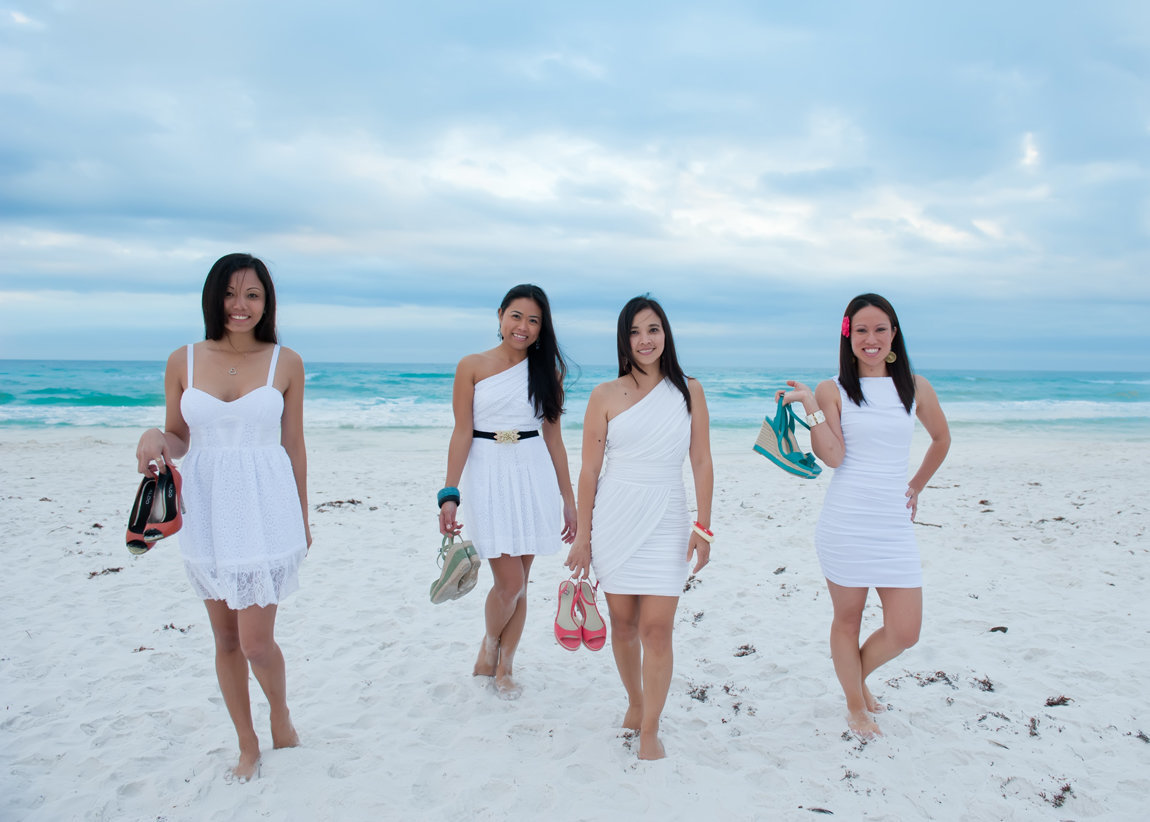 four friends walking on the beach with cute shoes in hand in Destin