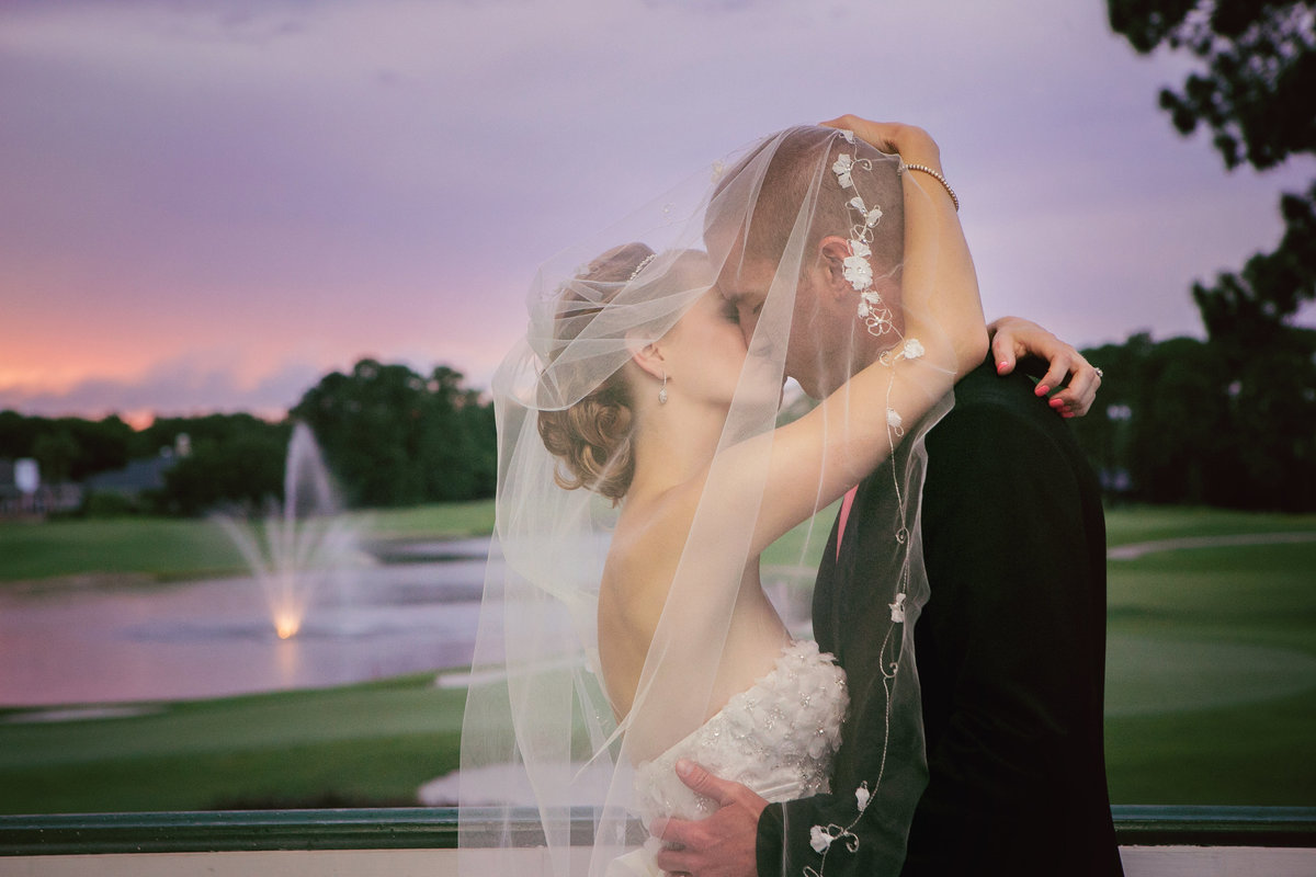 Bride and groom kissing at sunset at Jacksonville Golf and Country Club