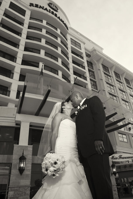 bride and groom kissing in front of renaissance north hills