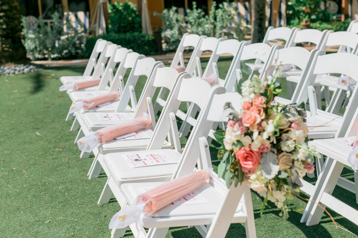 white wedding chairs with pink umbrellas on top
