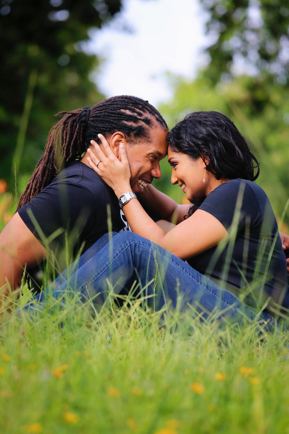 Couple sits together in idyllic field while gazing into each other's eyes. Photo by Ross Photography, Trinidad, W.I..