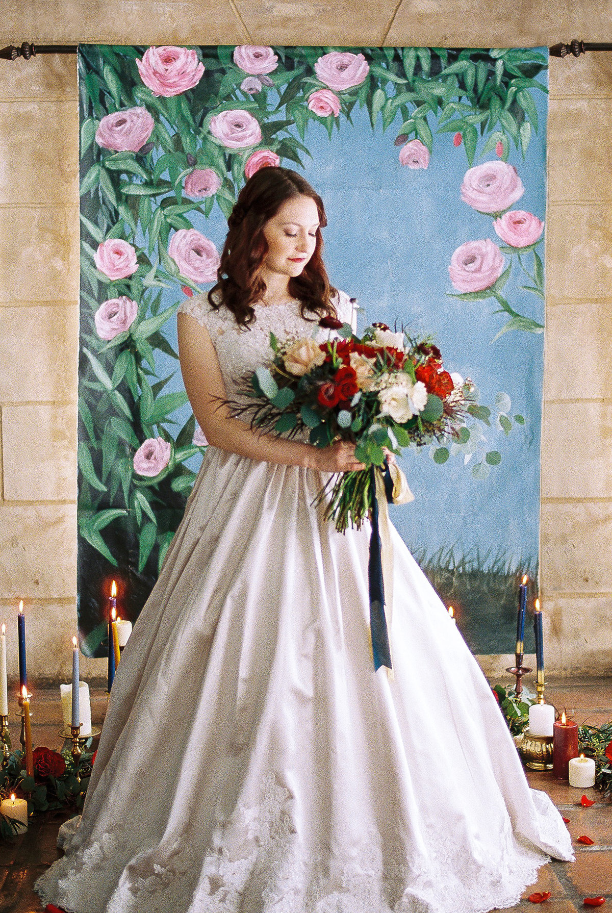 Bride standing in front of Beauty and the Beast inspired floral wedding backdrop By Brittany Branson as featured on Inside Weddings