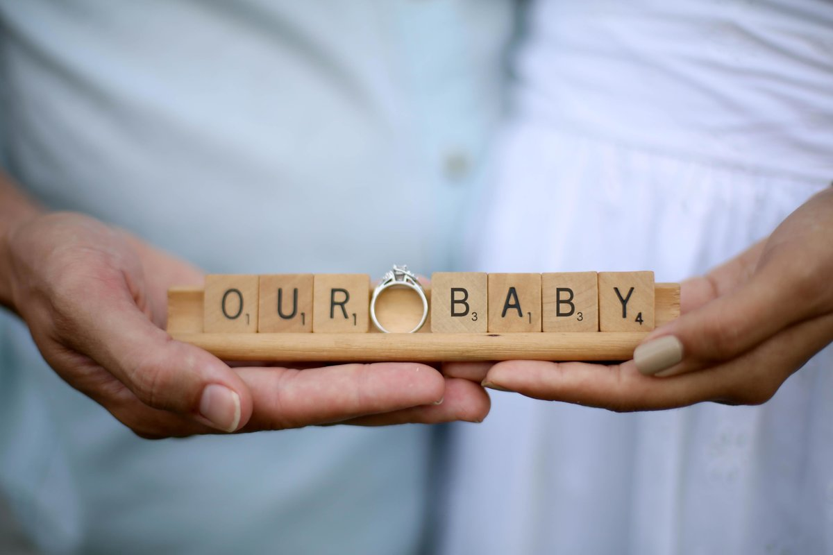 "Hands holding scrabble tiles spelling ""our baby"" with a wedding ring. Photo by Ross Photography, Trinidad, W.I.."