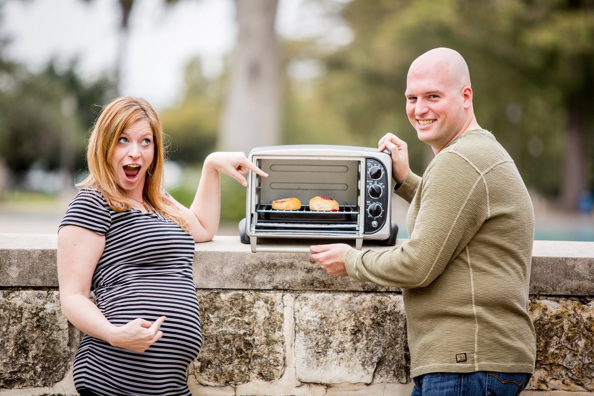 Twins Maternity session of woman and man pointing at buns in the oven at San Pedro Park in San Antonio.