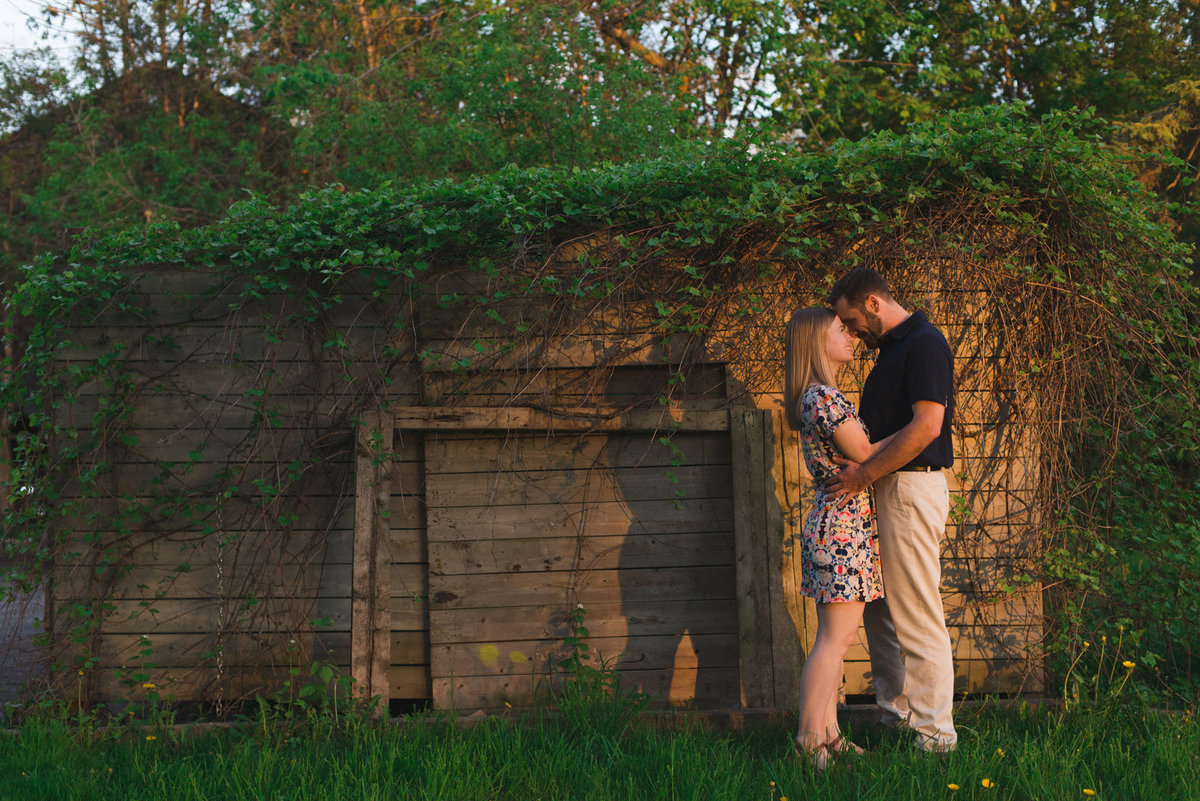 Couple standing in the sunlight against an old wooden shed with vines