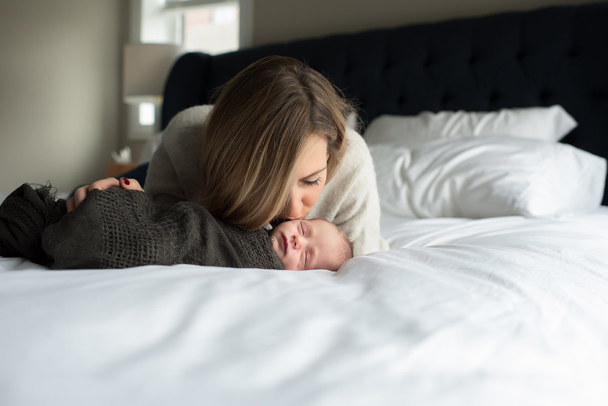 a new mom kisses her sleeping baby