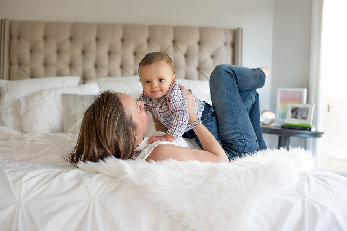 a mother tickles her son on the bed