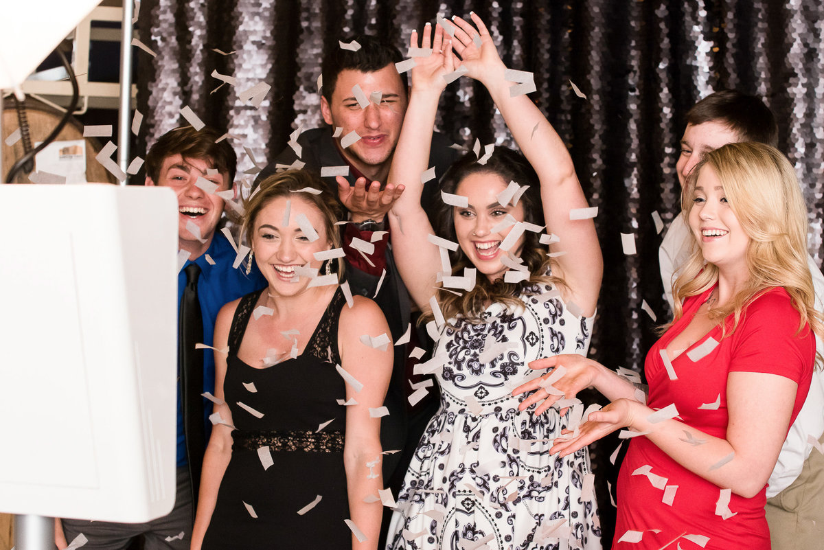 Party guests throw confetti for a photo booth pic