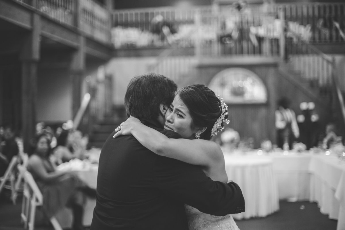 bride cries and hugs her dad during father daughter dance at The Grande Hall at Hoffman Ranch wedding venue in Castroville
