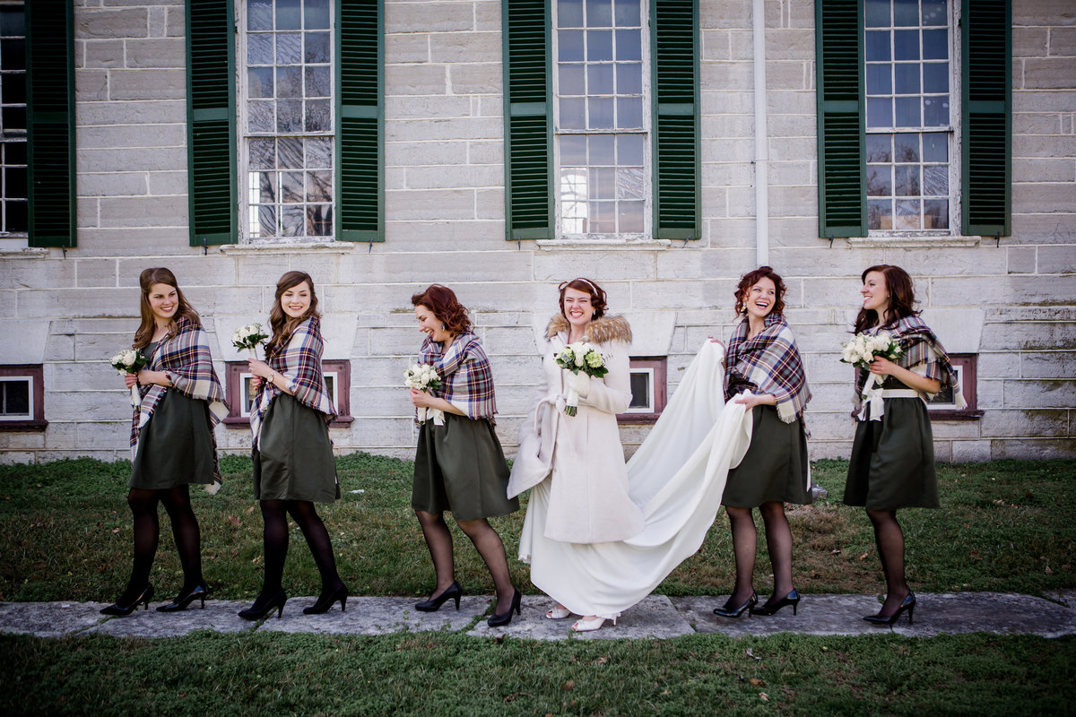 Bride and her bridesmaids walking in front of a historical building at Shaker Village in Lexington, KY by Knoxville Wedding Photographer, Amanda May PhotosBride and her bridesmaids walking in front of a historical building at Shaker Village in Lexington, KY by Knoxville Wedding Photographer, Amanda May Photos