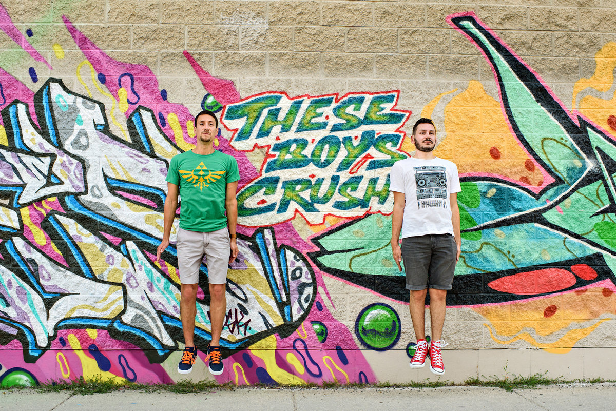 A same sex couple jump in front of a wall of graffiti in chigago that says, these boys crush.
