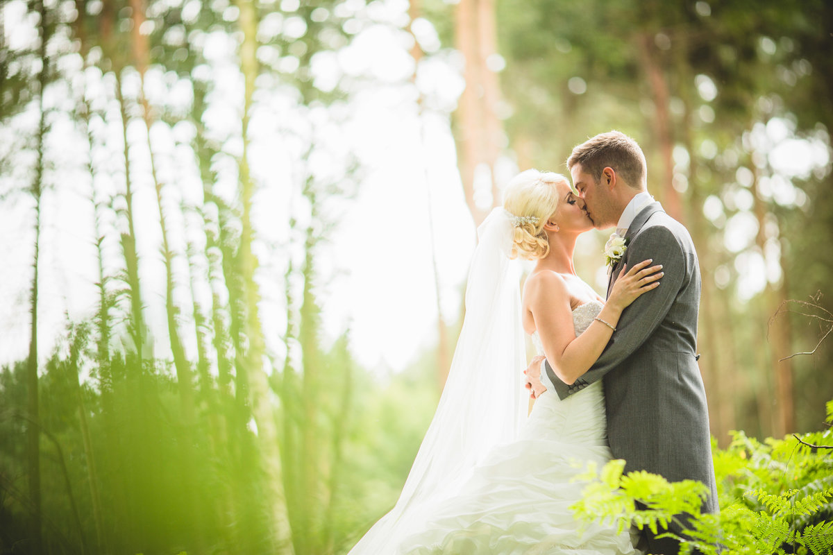 couple kissing in the forrest at peckforton castle