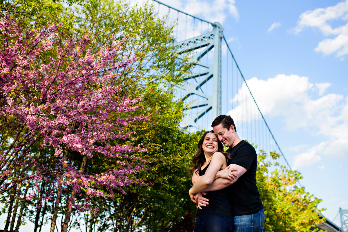 A man holds his girlfriend with the philly bridge in the background.