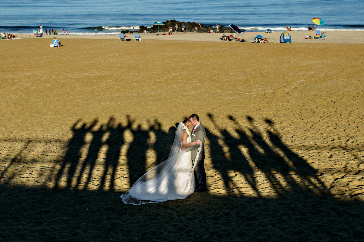 A bride and groom are surrounded by the shadows of their wedding party at this long branch new jersey wedding.