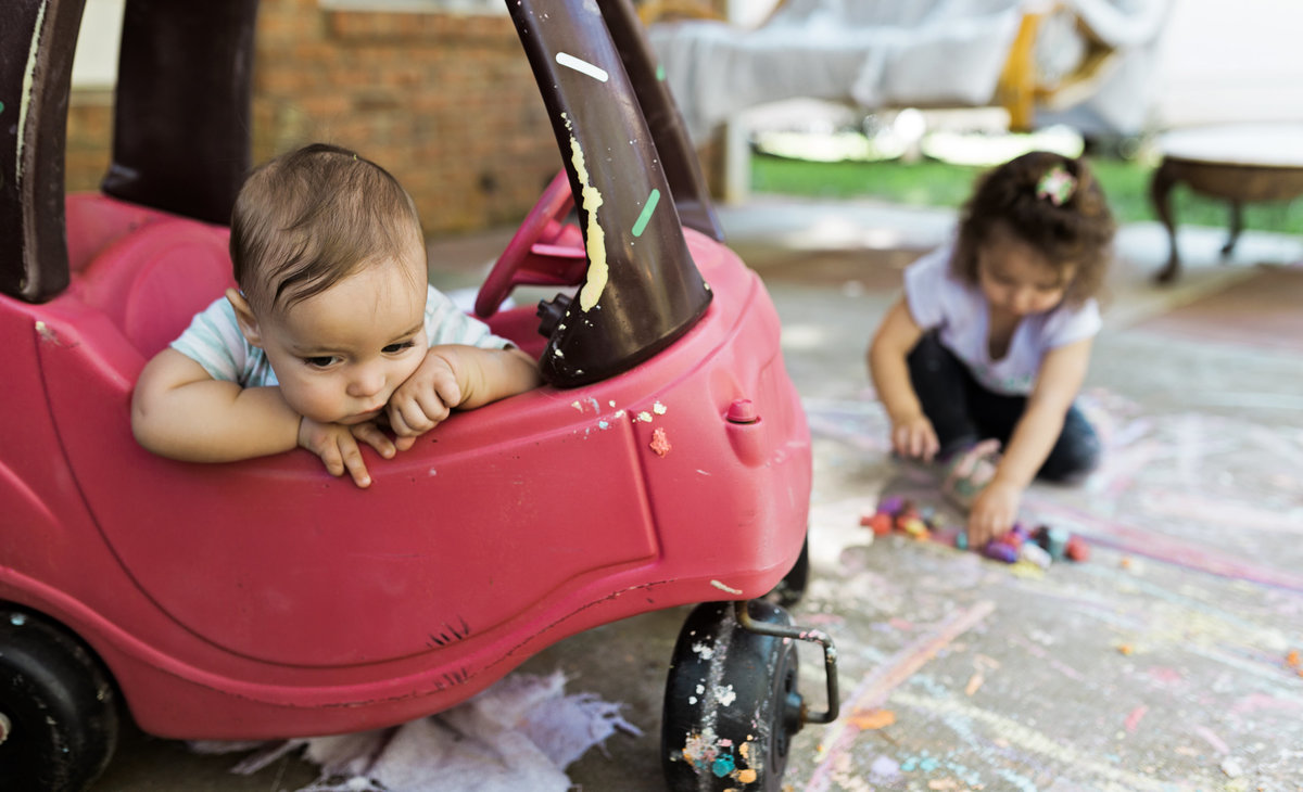 charlotte documentary photographer captures a day in the life of chilfren playing with cozy coupe and chalk