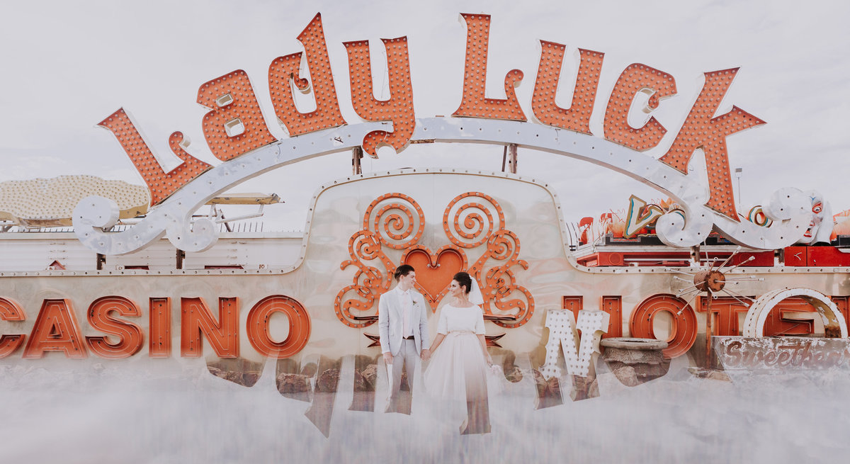 bride and groom marry under lady luck sign at neon museum