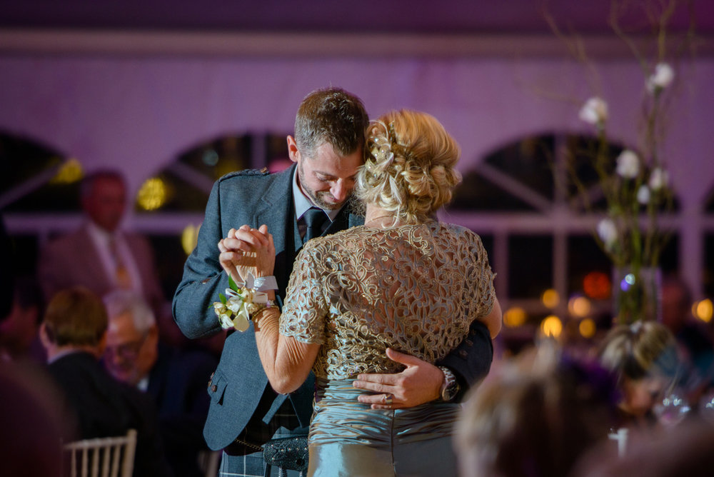 groom embraces mother during first dance