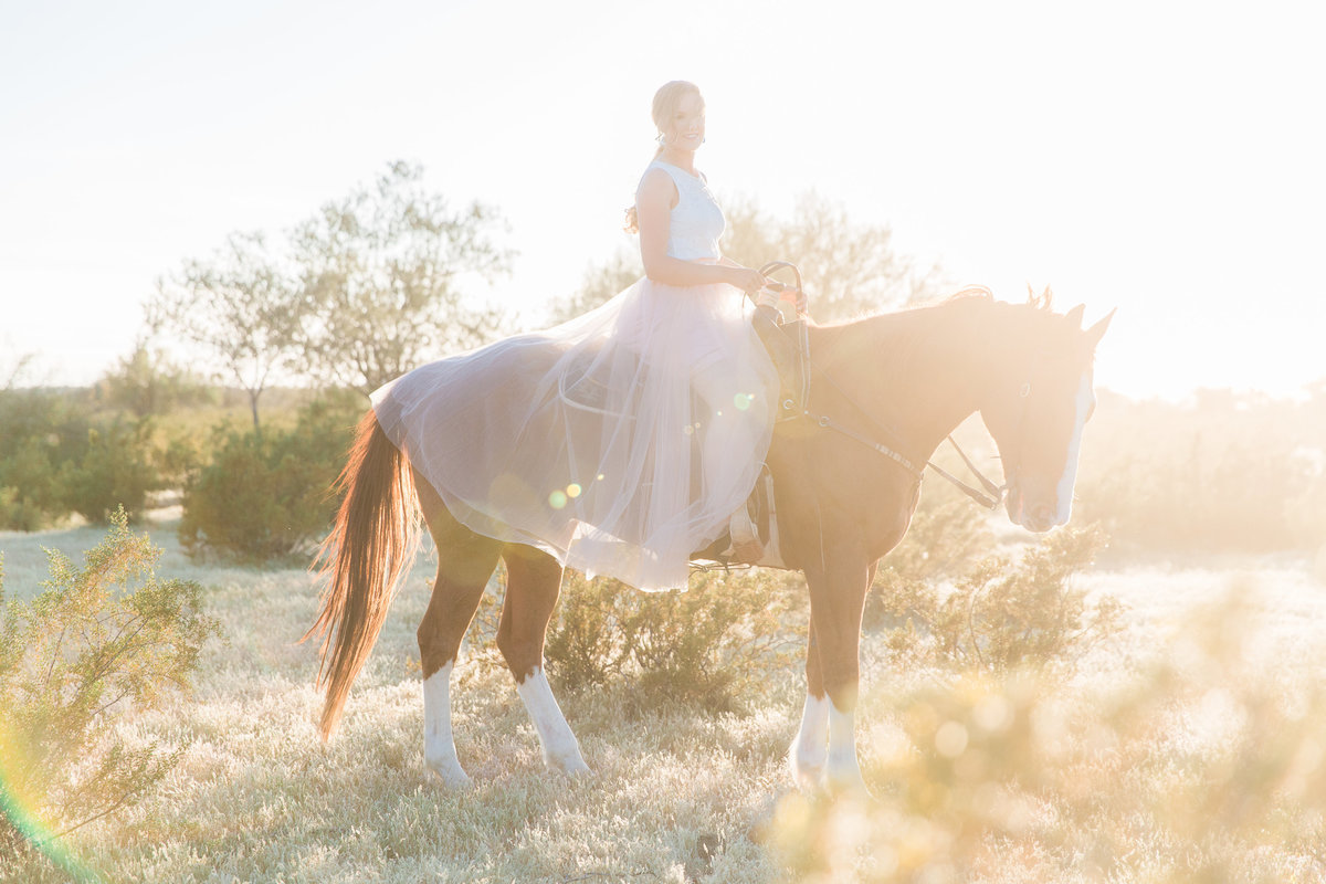 Golden hour portrait of a girl in a long white dress riding her horse in a field