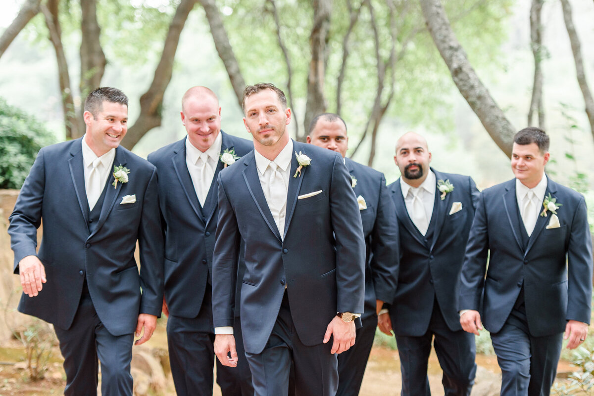 groom walking in the woods with ushers