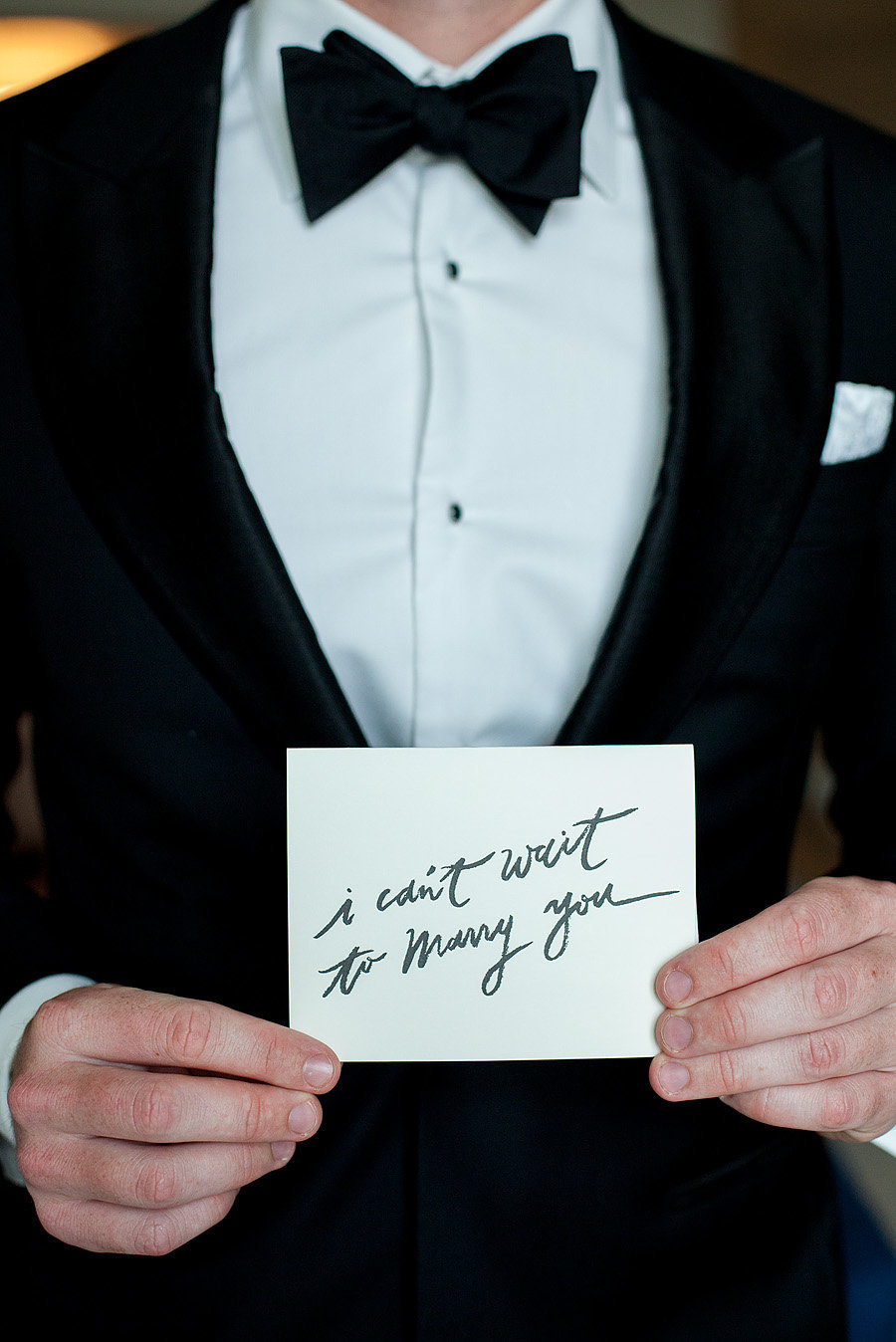 groom holding card that says i can't wait to marry you, flagler museum wedding