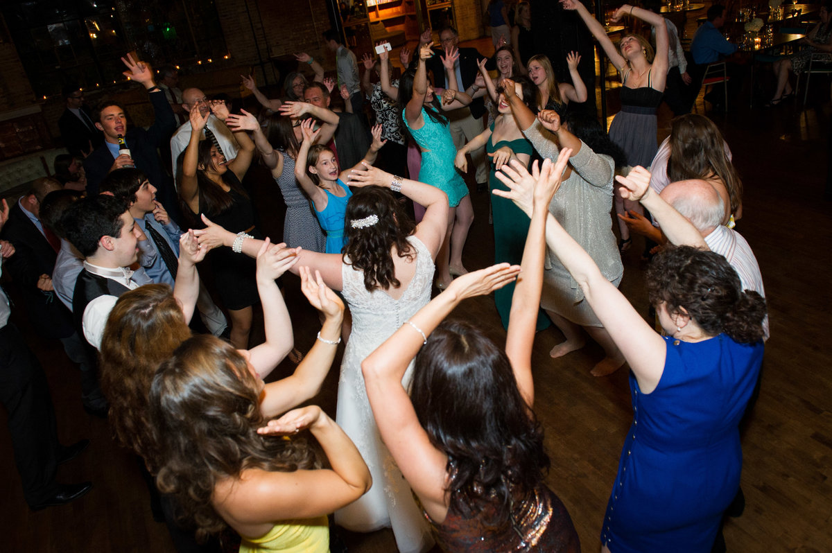 Guests dance with hands in the air, wedding reception, Chicago.