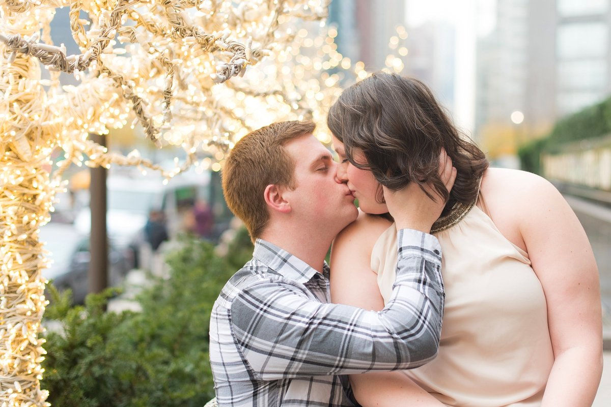 Couple kissing under white Christmas lights out front of Trump International in Columbus Circle, New York City Photo