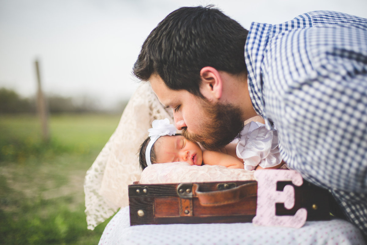 Father kissing his newborn daughter sleeping in a vintage suitcase in a field in San Antonio