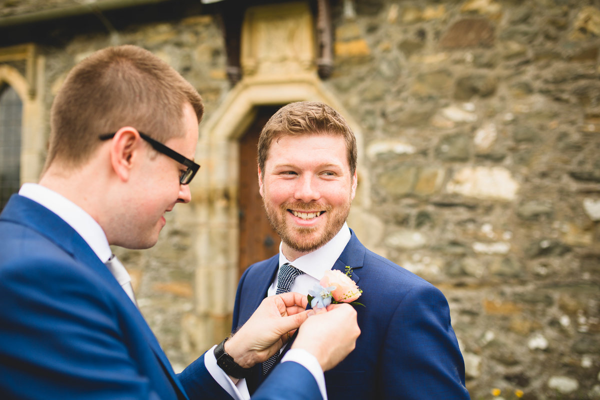 best man putting grooms buttonhole in