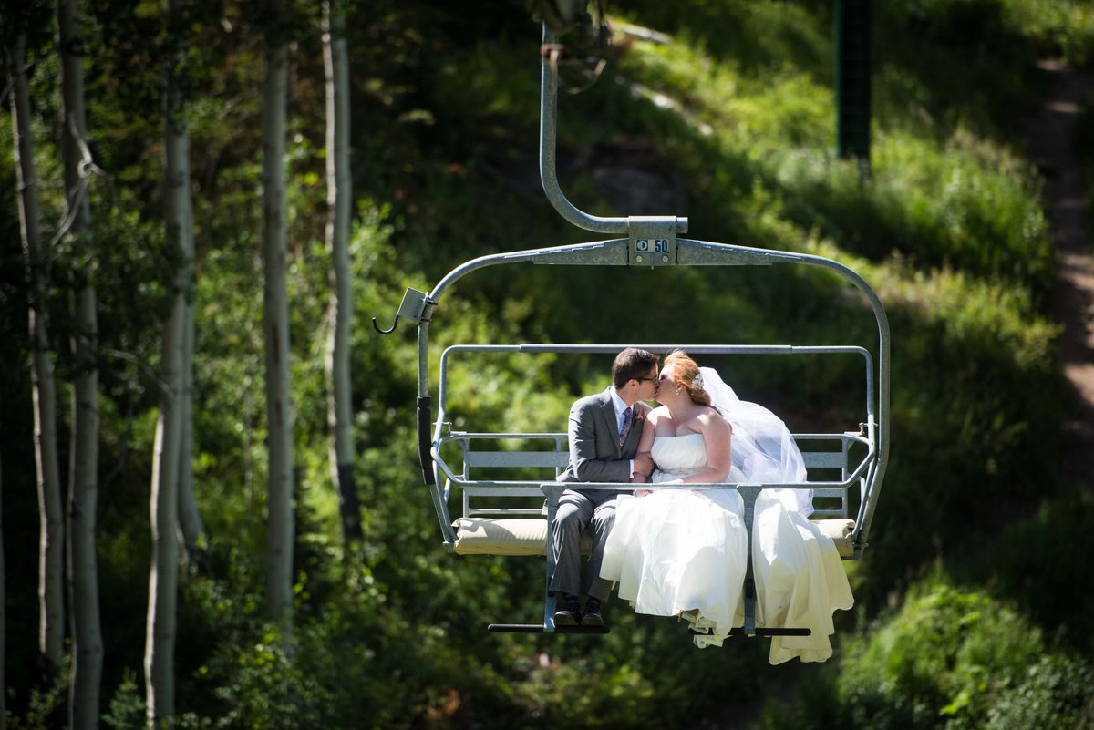 Bride and groom on ski lift for Park City, Utah wedding.