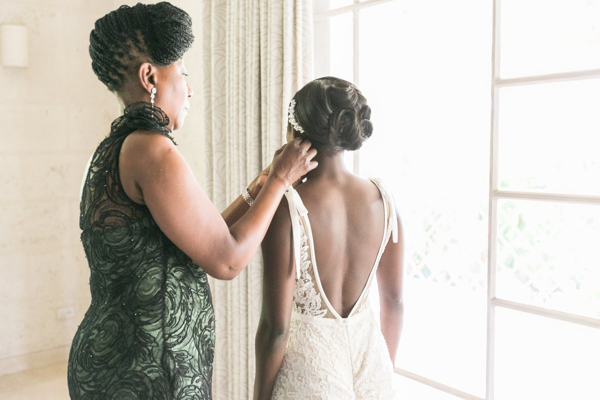 Mother helping bride with earrings on wedding day