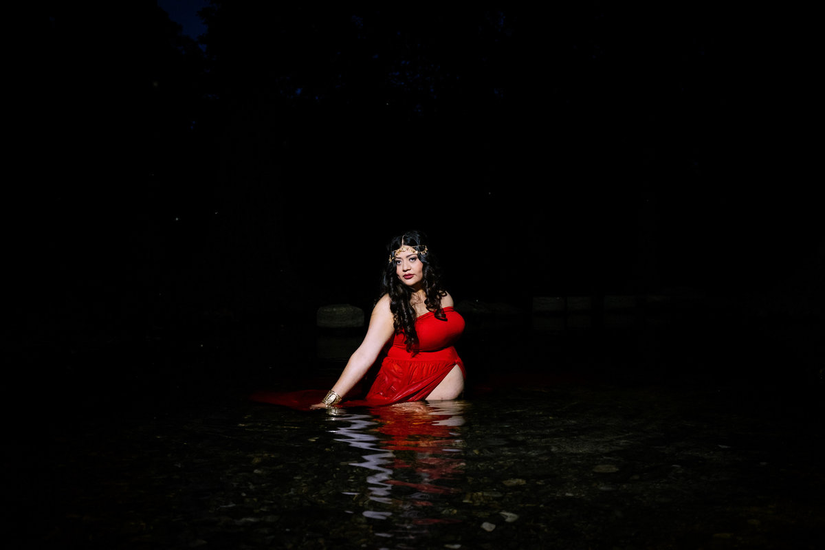 Pregnant woman in red maternity dress sitting in river water in Cibolo Nature Center.