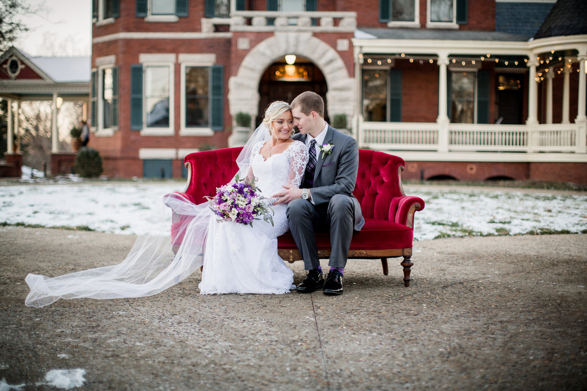 Bride and groom cuddle on vintage couch in front of Historic Westwood Wedding Venue by Knoxville Wedding Photographer, Amanda May Photos.
