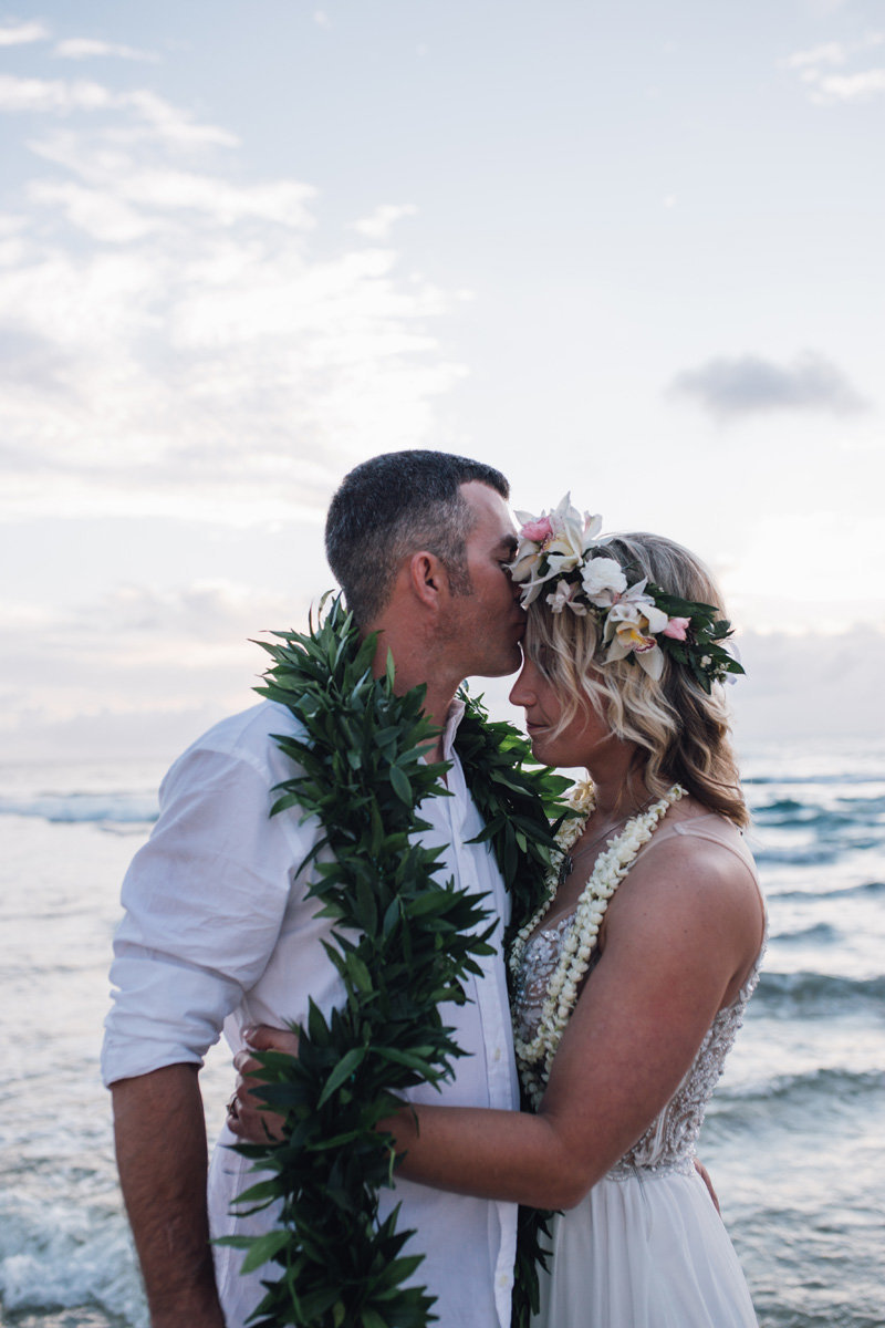groom kissing brides forehead by the ocean with a male lei and she is wearing a haku lei