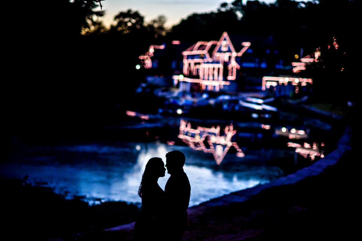 An engaged couple silhouetted in the water with boathouse row in the background.