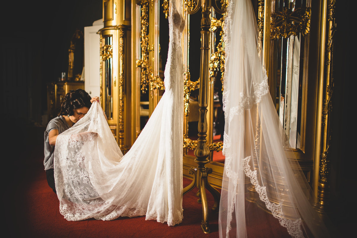 a bride at allerton castle is adjusting her hanging lace wedding dress in front of a gold mirror