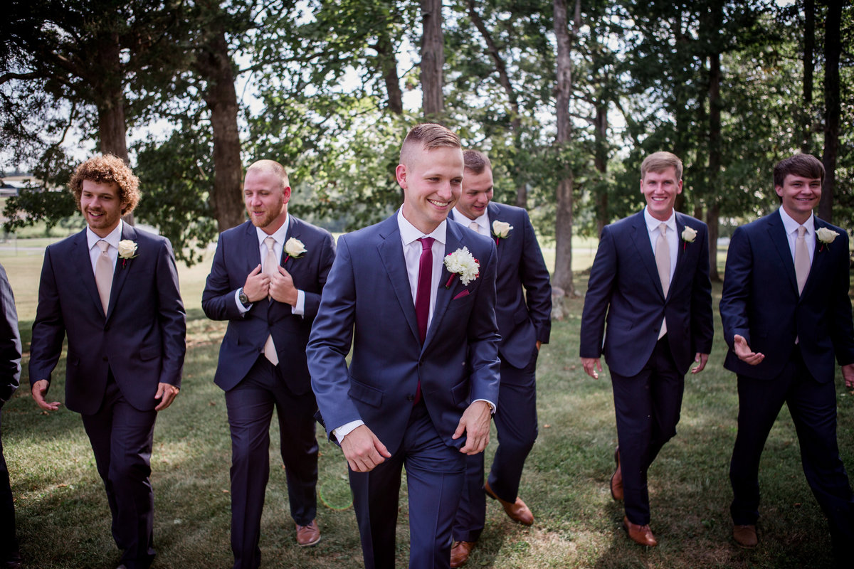 Groom and groomsmen walking towards camera at small white chapel wedding by Knoxville Wedding Photographer, Amanda May Photos.