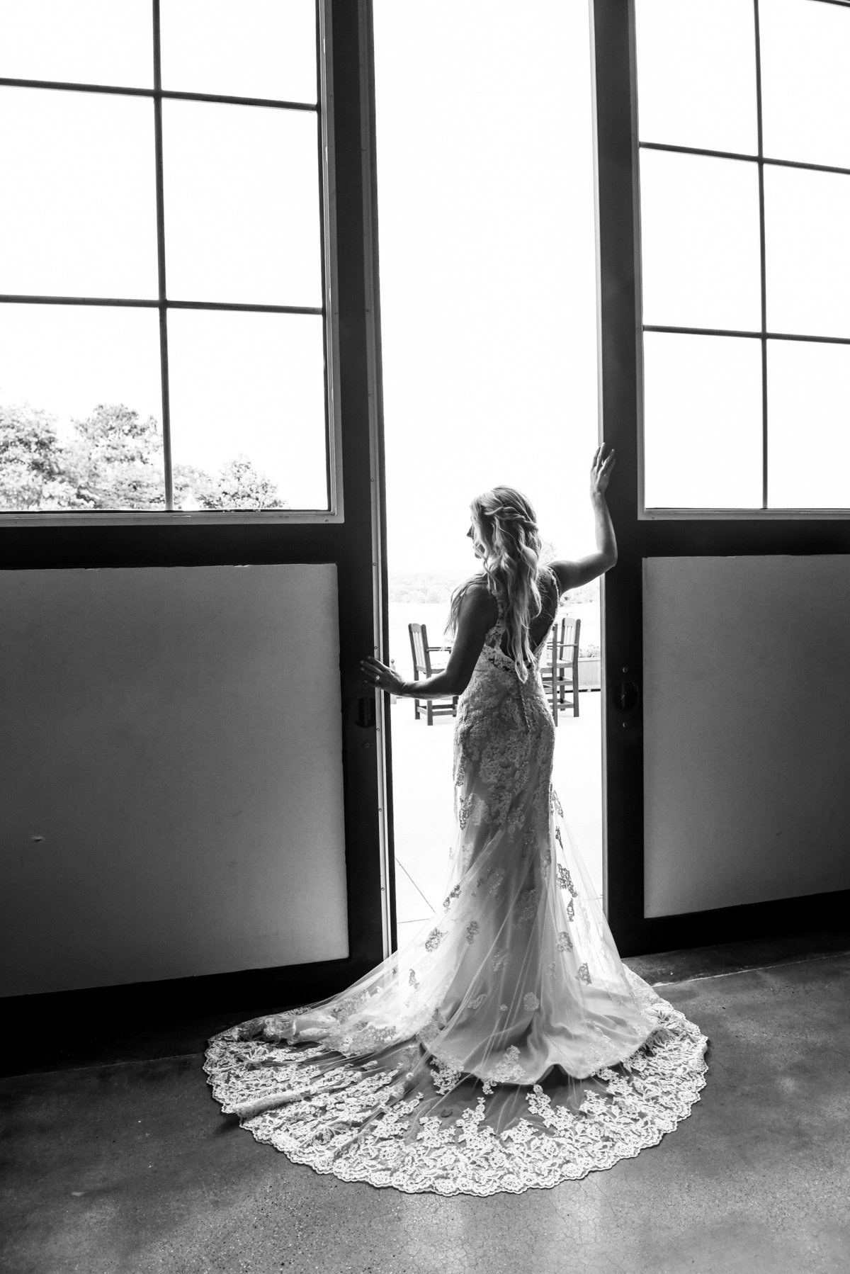 Black and white image of a stunning bride posing at a barn door at Mount Ida Farm in Charlottesville. Richmond and Charlottesville wedding photographers
