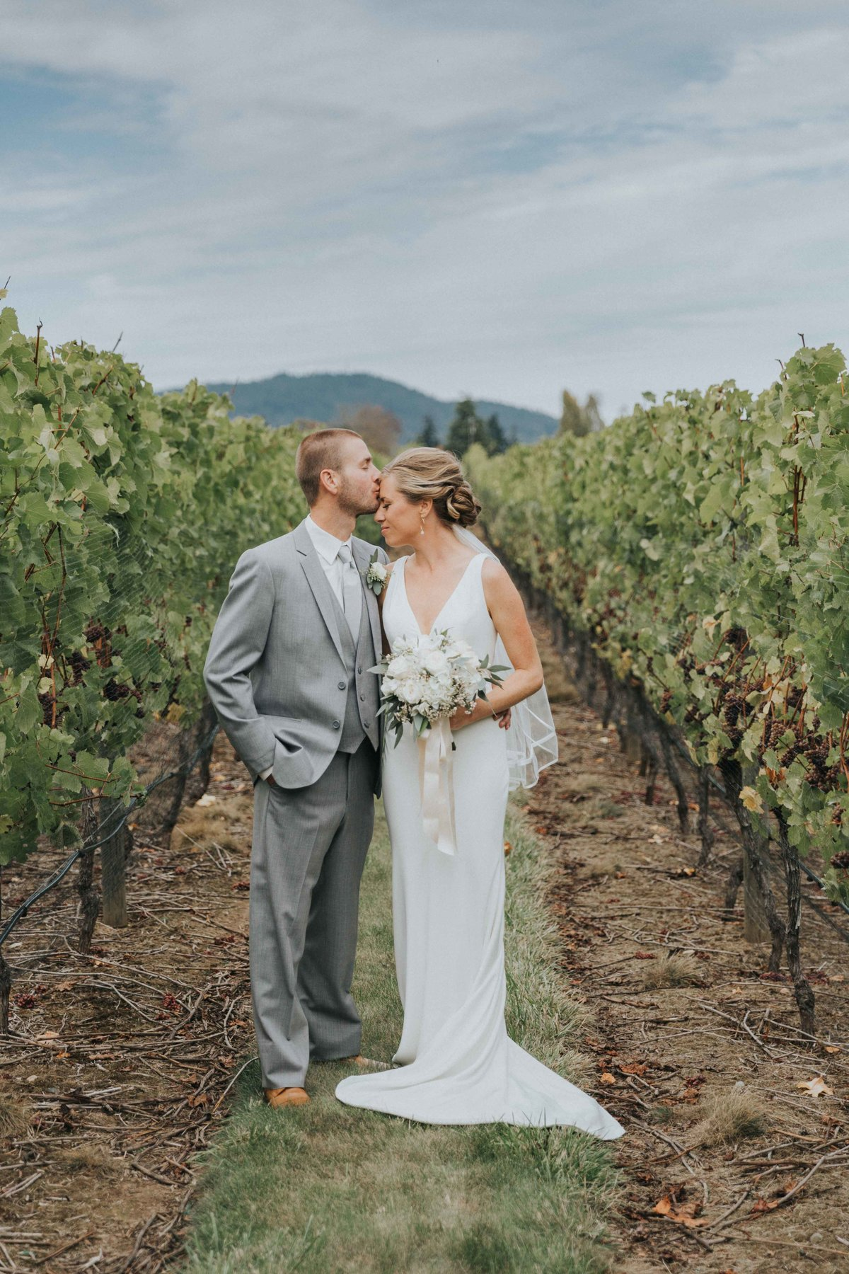 Beautiful wedded couple standing in the orchards at Church and State Winery, Victoria BC