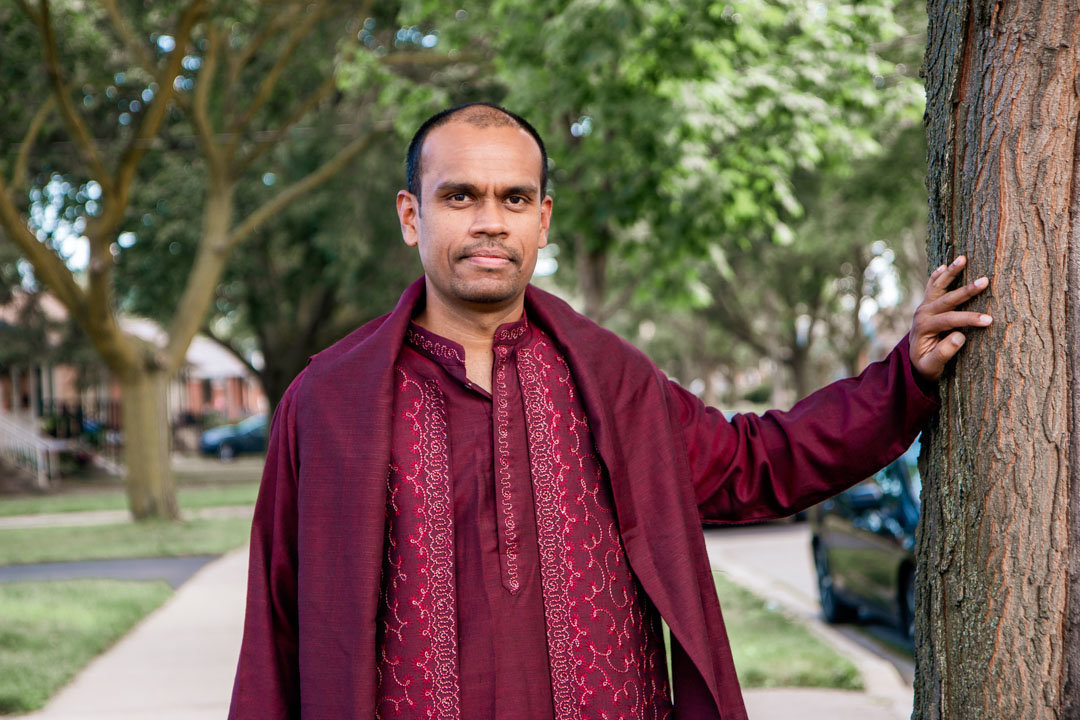 groom in his  dark red indian attire with one hand against a tree trunk