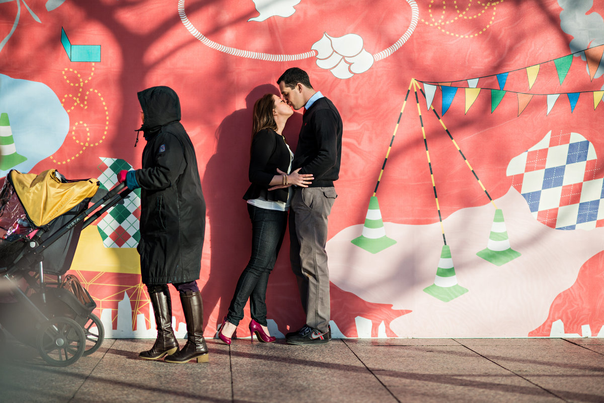 A couple kiss while pass them by on the nyc streets.