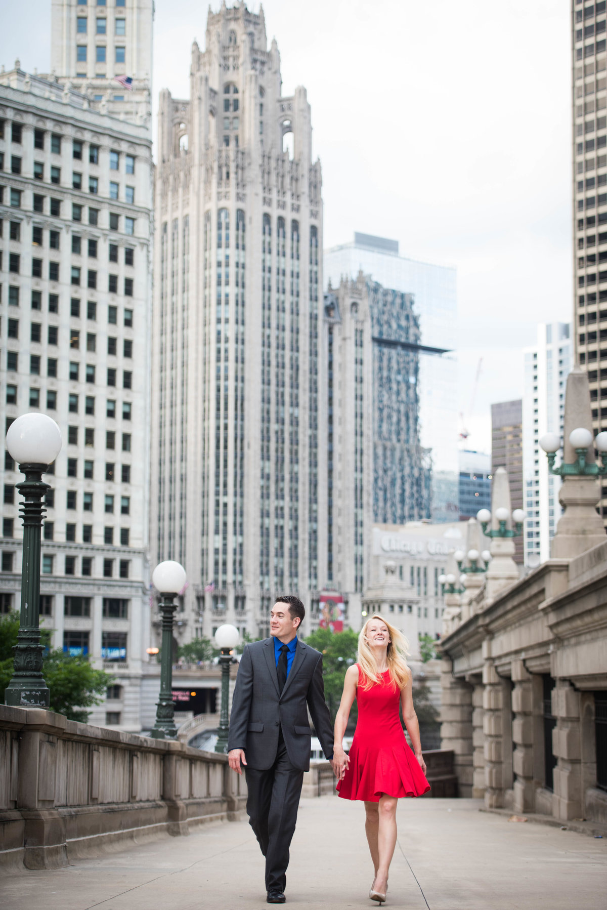 Engaged couple, Chicago, walks Riverwalk, Wrigley Building skyline.