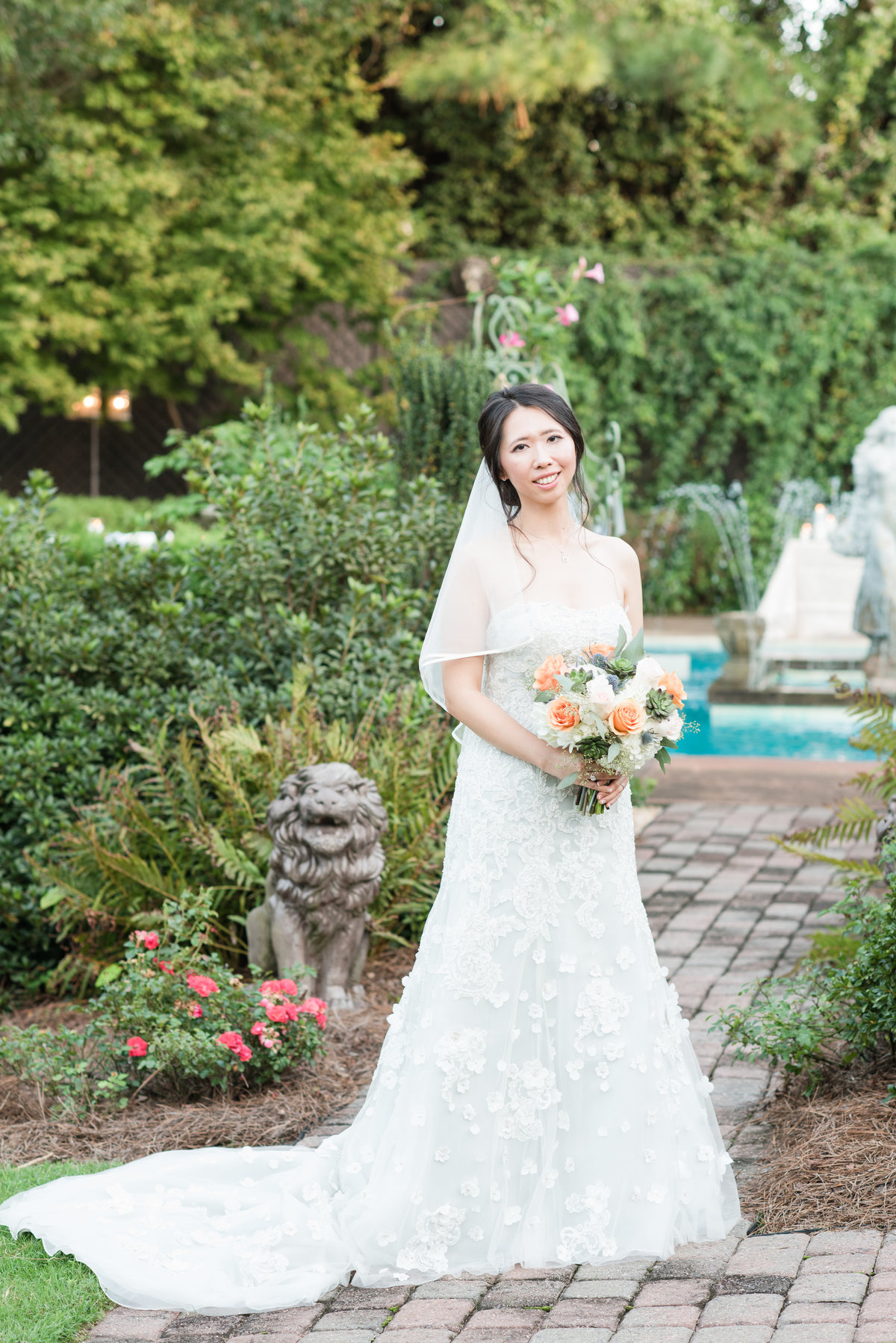 a bride wearing a strapless light blue wedding dress with mid-length veil holding white and orange wedding bouquet in front of an elegant little garden with pond at Barclay Villa