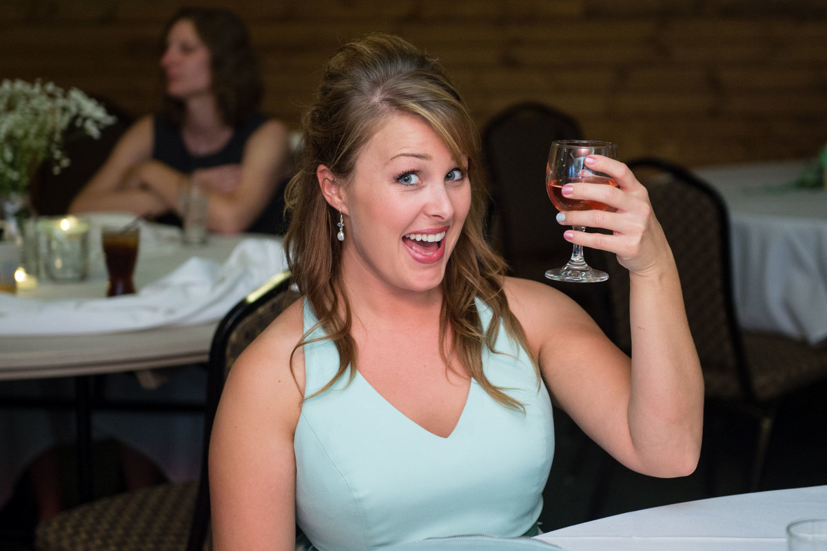 bridesmaid holds up wine glass to photographer