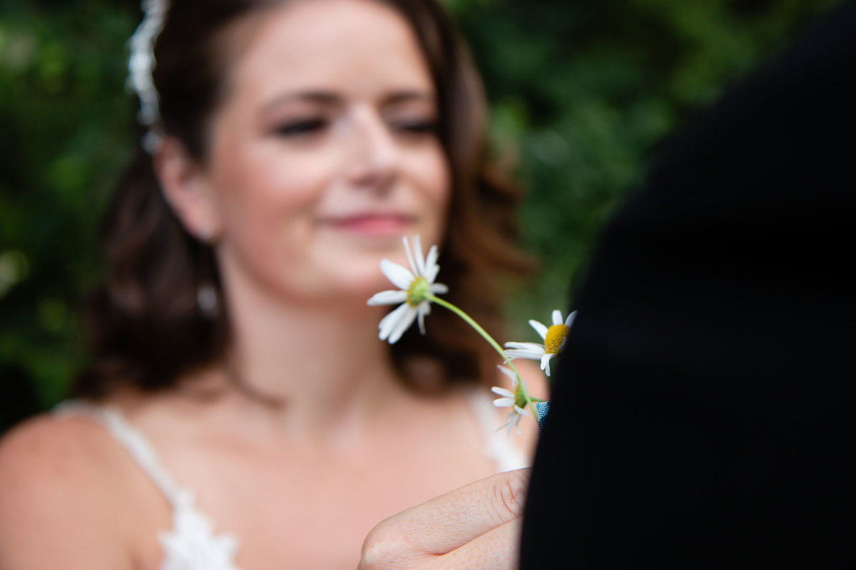 The bride put a daisy into her grooms pocket and the focus is on the flower for this wedding portrait