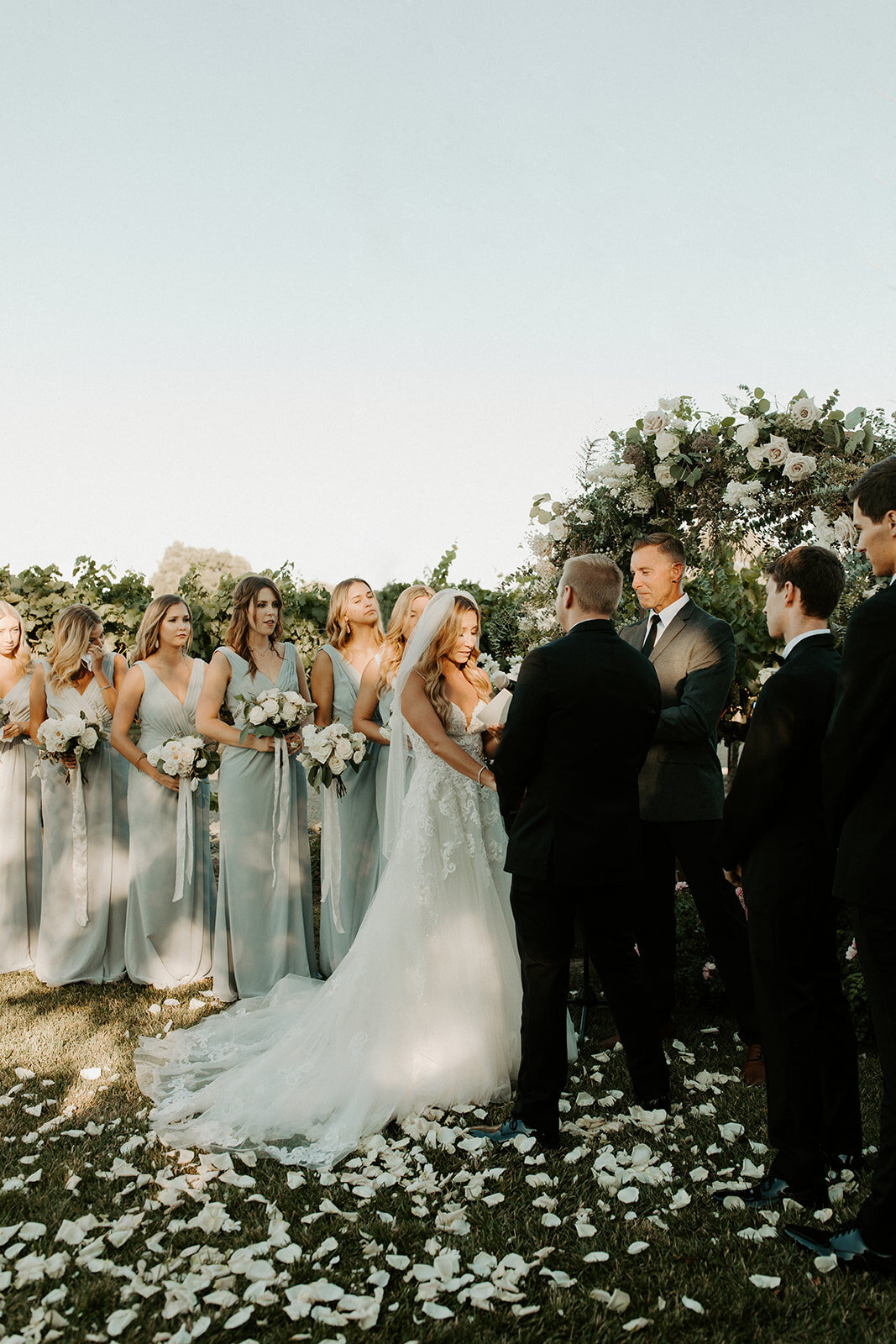 bridal party standing in front of foral arch
