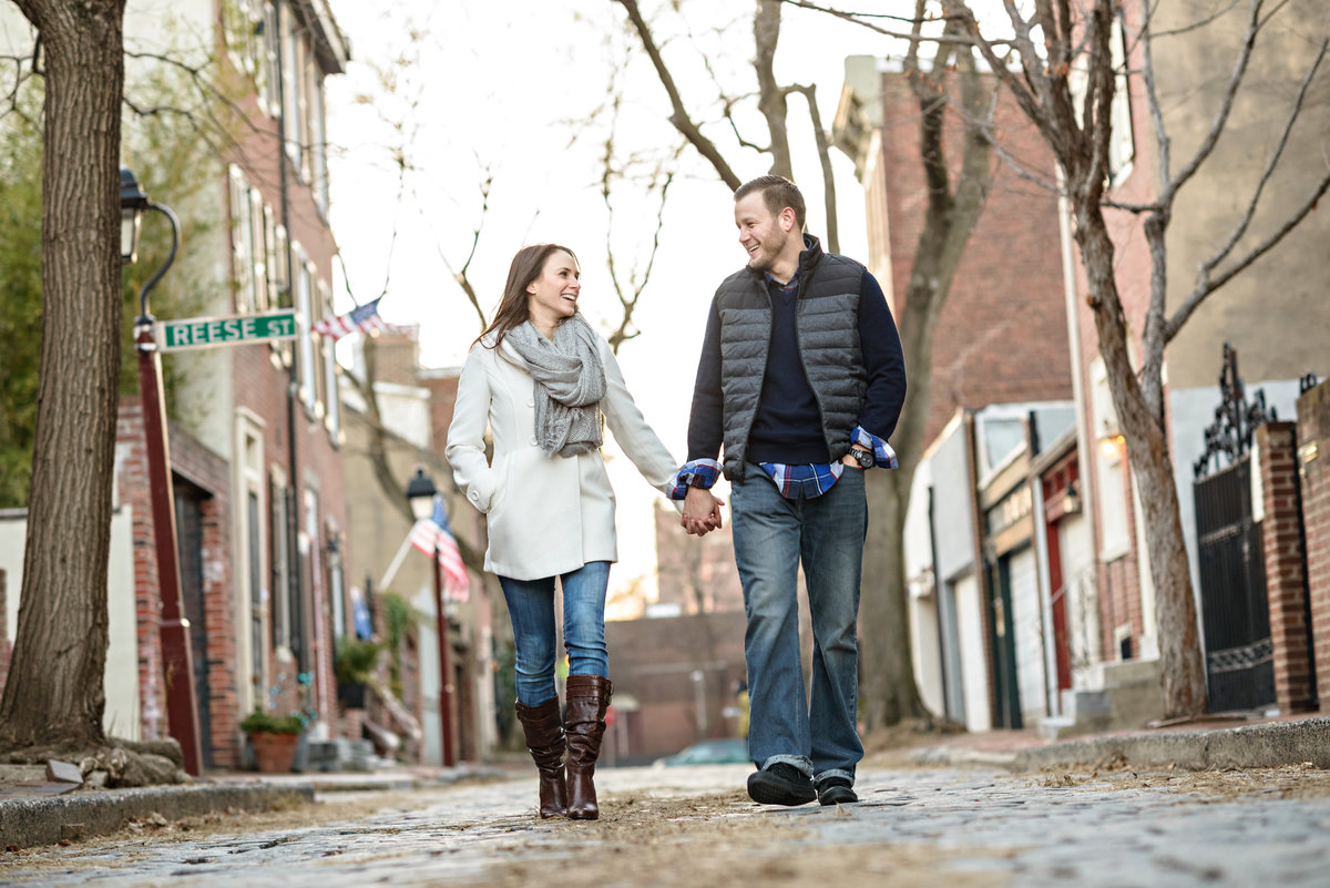 Two engaged people walk the cobblestone streets of old city philadelphia.